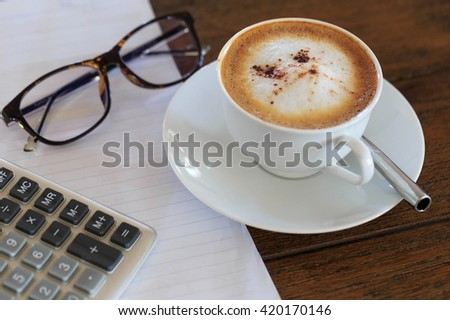 Coffee cup and notebook with calculator and glasses