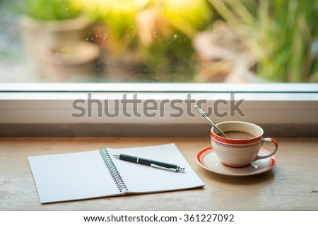 Coffee cup and opened notebook with pen on wood bar beside window at coffee shop in morning time