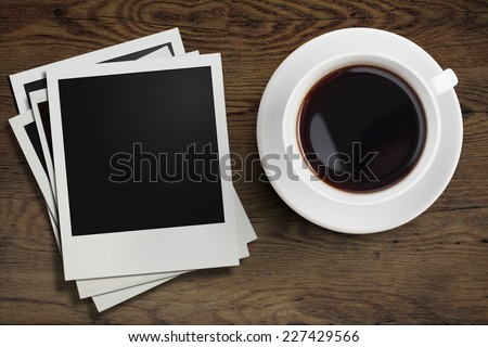 coffee cup and polaroid photo frames on wooden table - stock photo