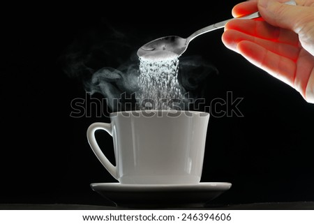 Coffee cup and pouring sugar spoon on white background - stock photo