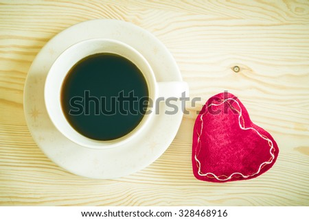 coffee cup and red heart on wooden table + vintage filter - stock photo
