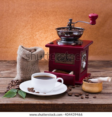 Coffee cup and saucer, coffee grinder, coffee beans in sack and spilled on  wooden table. Dark background.