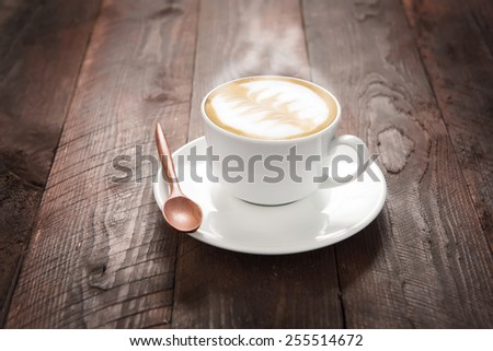 Coffee cup and saucer on a wooden table.  - stock photo