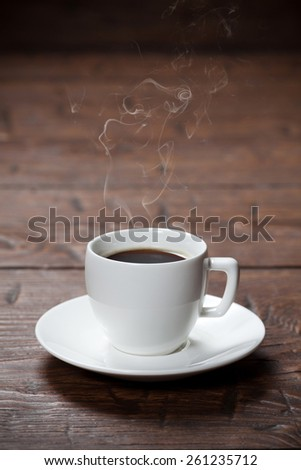 Coffee cup and saucer on old wooden table - stock photo