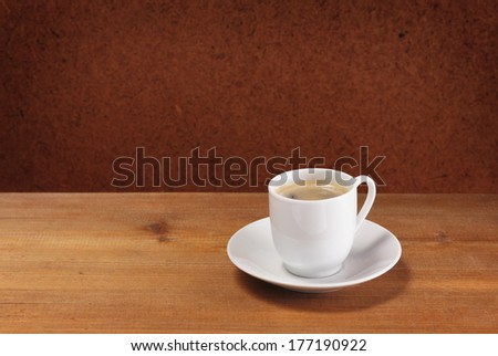Coffee cup and saucer on wooden table. Dark background.