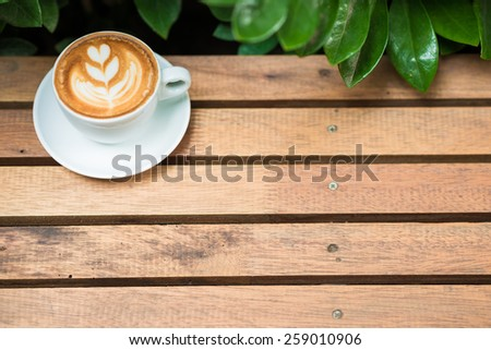 Coffee cup art tree face on wood table with green leave frame, Coffee art - stock photo
