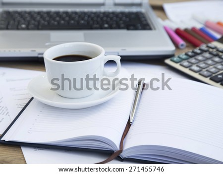 Coffee Cup at Office Placed over Paperwork and Agenda with Pen,Calculator and Laptop in the Background - stock photo