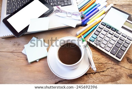 Coffee Cup at Office with Tablet and Laptop, Electronic Computer , Glasses and Pencils on Wooden Desk - stock photo