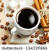 Coffee cup, beans, cinnamon, sugar and anise on a table - stock photo