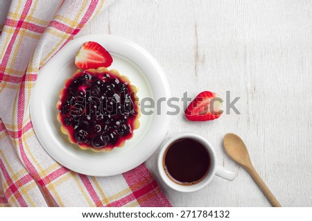 Coffee cup, cake with black currants and strawberry on table, top view - stock photo