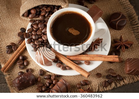 Coffee cup, chocolate and beans on a rustic background. Coffee Espresso. Cup Of Coffee, anise, cinnamon and coffee beans on table.