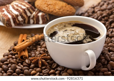 Coffee cup, cinnamon, anise on coffee beans, sweets on the background - stock photo
