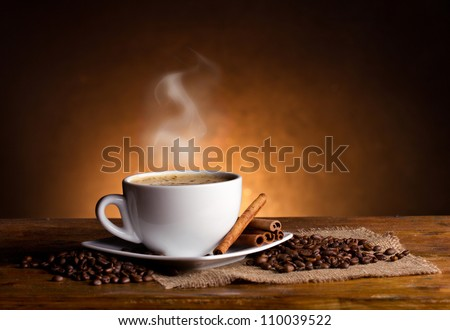 coffee cup, coffee beans and cinnamon sticks on dark background
