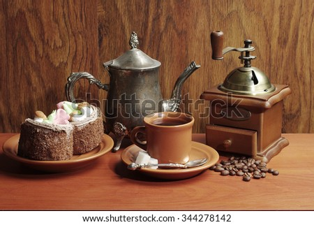 Coffee cup, coffee grinder and cakes