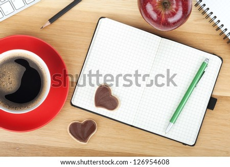Coffee cup, cookies, red apple and office supplies on wooden table
