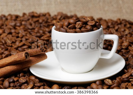 Coffee cup demitasse full of coffee beans and cinnamon sticks in the heap coffee beans on burlap background - stock photo