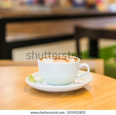 Coffee cup in coffee shop interior - stock photo