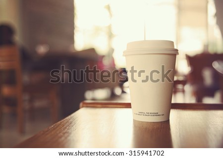 coffee cup in coffee shop with vintage filter - stock photo