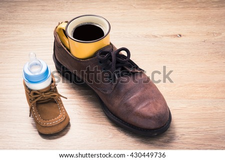 coffee cup in father shoes and milk bottle in child shoes, love and bound concept
