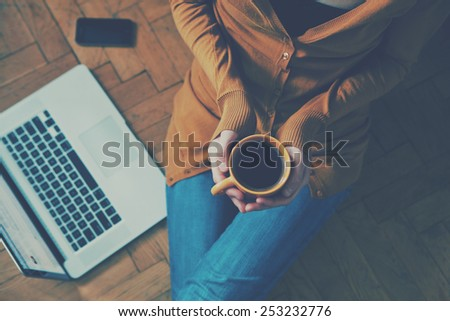 Coffee cup in girl's hands sitting on a wooden floor - stock photo
