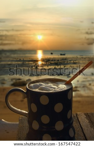 Coffee cup in the morning on terrace with sunrise background - stock photo