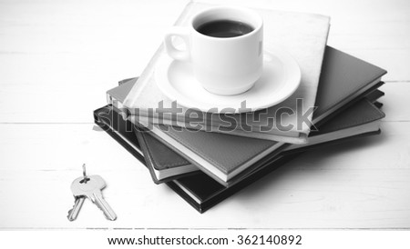 coffee cup,key and stack of book on white wood table black and white color