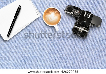 Coffee cup note pad and vintage camera on jean tablecloth background top view flat lay copyspace