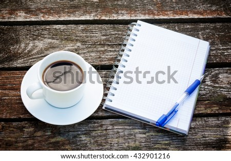 Coffee cup, notepad  and pen on wooden background