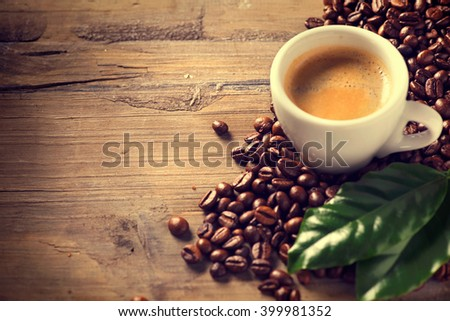 Coffee. Cup Of Espresso Coffee on wooden background decorated with coffee beans and green leaf of coffee plant. Copy space for your text. Vintage sepia toned - stock photo