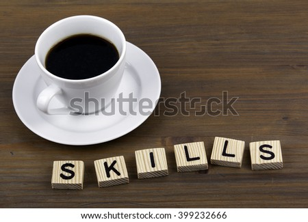 Coffee cup on a wooden table and text - SKILLS - stock photo