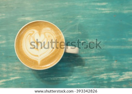 coffee cup on a wooden table ,Vintage color tone - stock photo