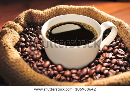 Coffee cup on coffee beans in burlap sack - stock photo