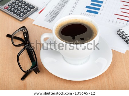 Coffee cup on contemporary workplace with financial papers, glasses and office supplies