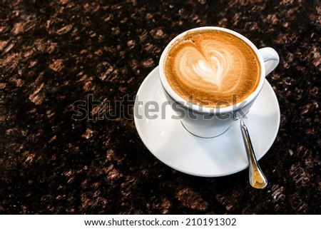 Coffee cup on marble table.Latte art heart shape. - stock photo