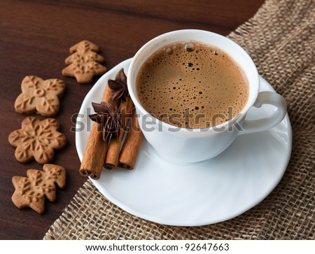Coffee cup on sacking material with cinnamon stick and cookies - stock photo