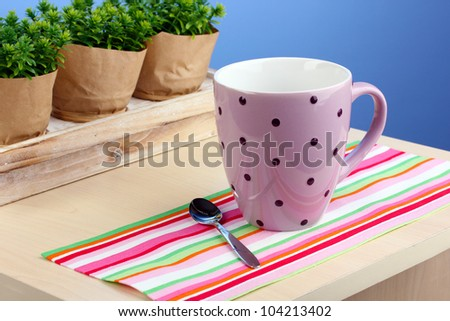 Coffee cup on table in cafe on blue background