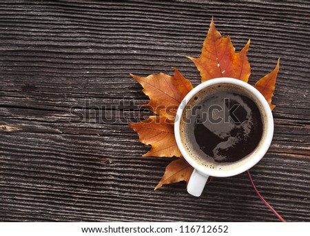 coffee cup on the autumn fall  leaves and wooden surface background - stock photo