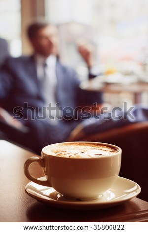 Coffee cup on the edge of the table - stock photo