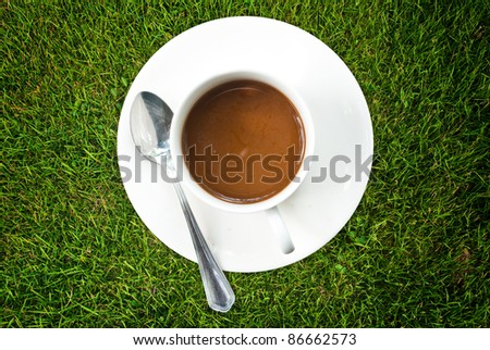 Coffee cup on the grass texture. - stock photo