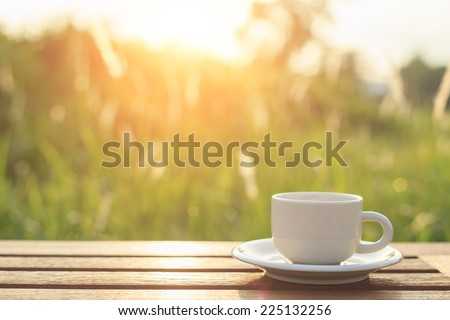 Coffee cup on the table in the morning - stock photo