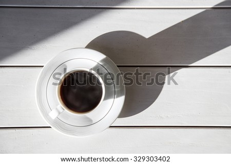coffee cup on white table with shadow