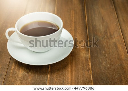 Coffee cup on wood table in morning sunlight.