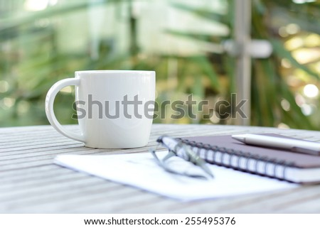 Coffee cup on wood table with notebook, pen & eye glasses