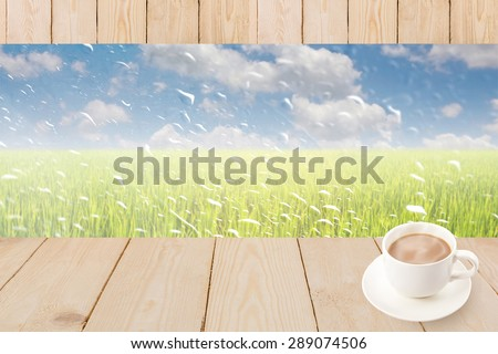 Coffee cup on wood texture with rain drops on a window or water drops on grass blurred with green rice field and blue sky. - stock photo