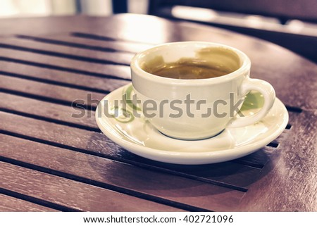 Coffee cup on wooden table , vintage tone [blur and select focus background]