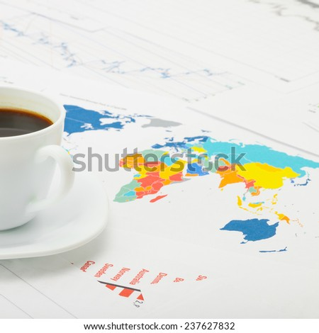 Coffee cup over world map and financial documents - business concept