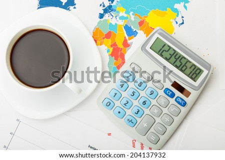 Coffee cup over world map and financial documents - view from top - stock photo