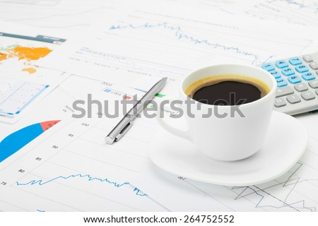 Coffee cup over world map and some financial charts - stock photo