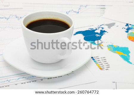 Coffee cup over world map and some financial documents - business concept - stock photo