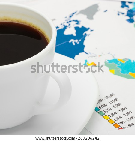 Coffee cup over world map - close up shot - stock photo